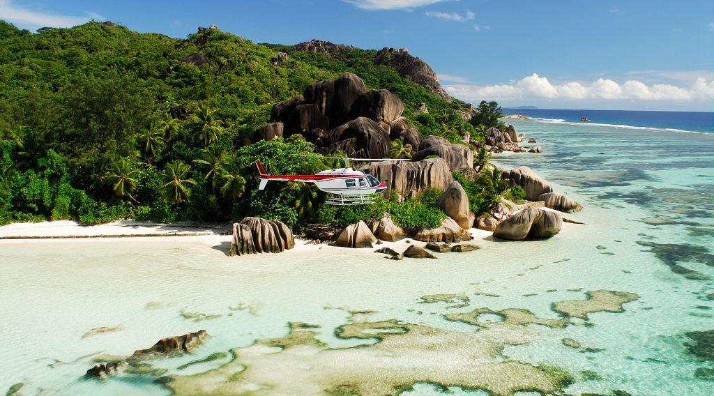 helikopter som flyr over vakker strand med steinformasjoner i granitt