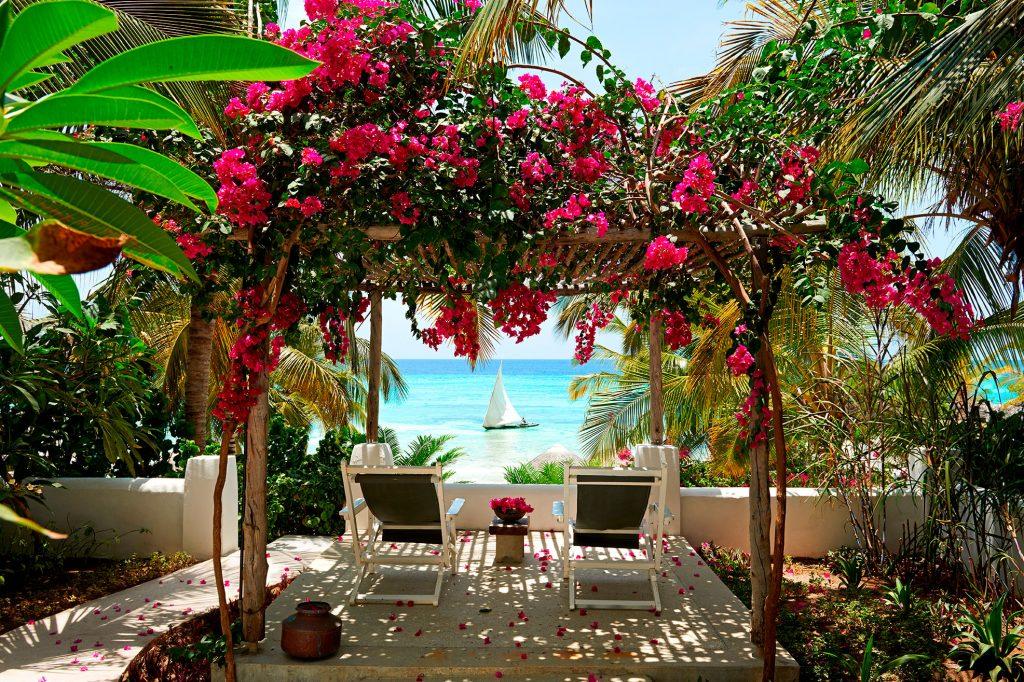 sitteplass med utsikt over havet med blomsterkrans av rosa blomster