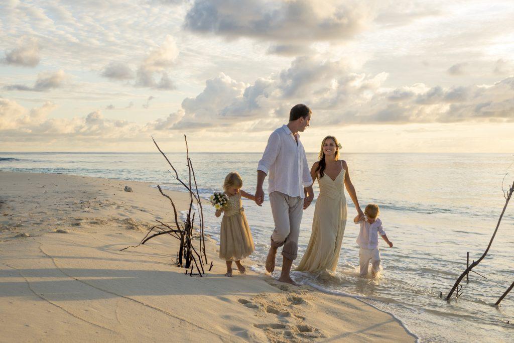 brudepar og liten brudepike og brudesvenn på stranden