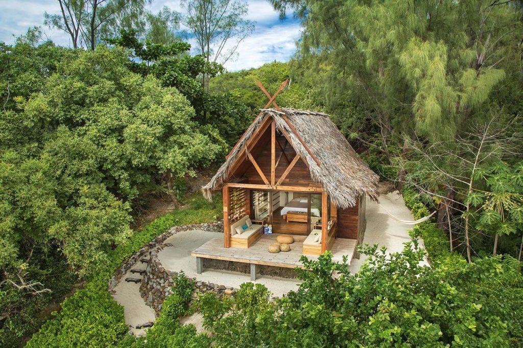 nydelig liten bungalow midt i tropisk vegetasjon på stranden
