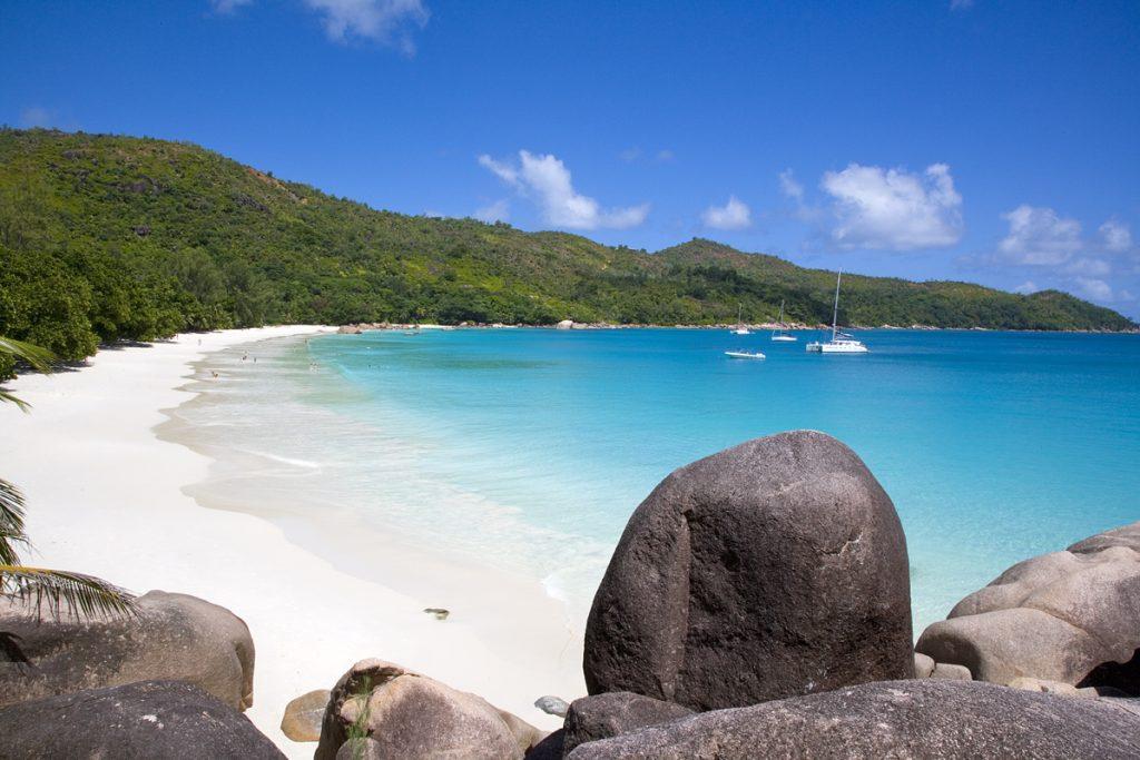 Langstrakt hvit strand med granittsteiner og turkist hav
