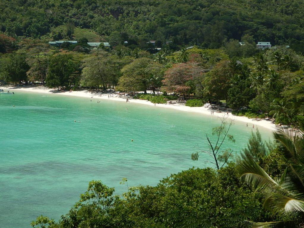 Lang sandstrand i en bukt omgitt av grønn og frodig vegetasjon med turkisblått hav og mennesker både i havet og på stranden. Hotellanleggets tak er synlig mellom trærne