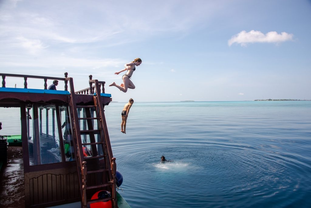 barn som hopper fra taket på en båt og ut i vannet