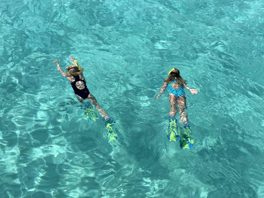 To små piker snorkler i turkist vann