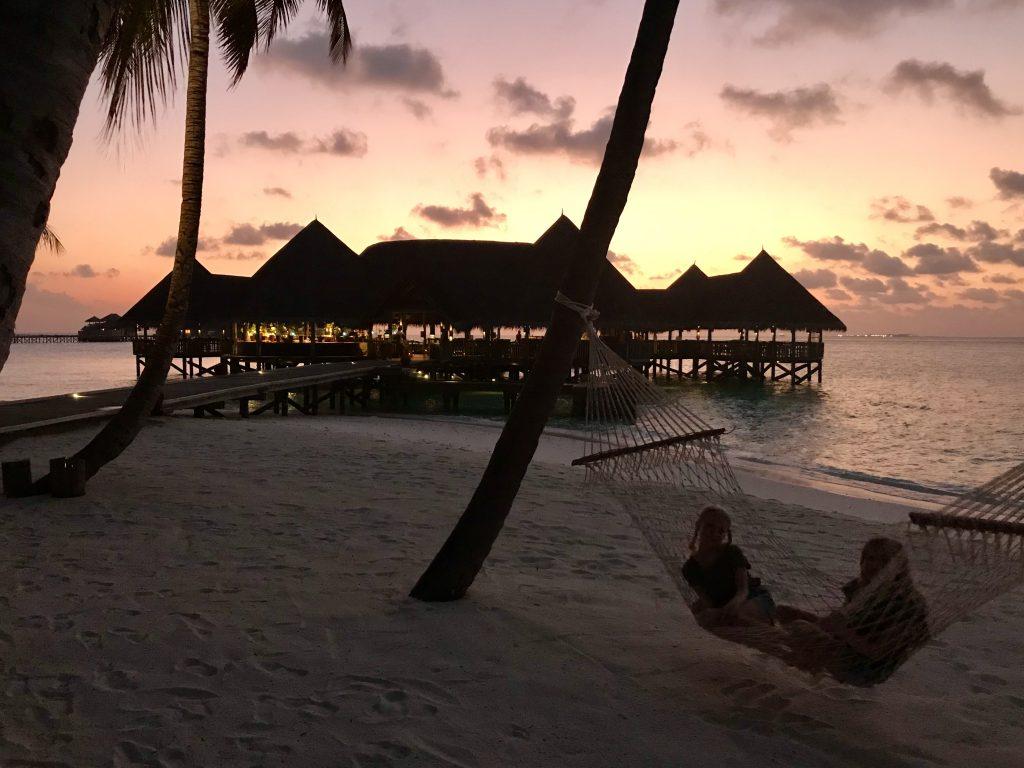 Rød solnedgang med palmer og hengekøye på stranden og villaer i bakgrunnen